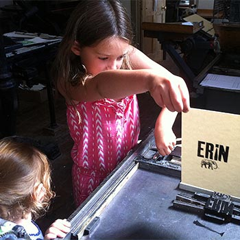 Justin & Cecilia's eldest daughter Freya printing wood type on a proofing press